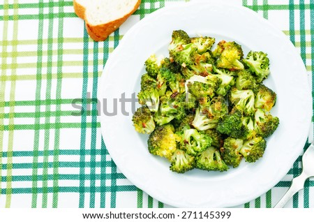 roasted broccoli with garlic on a green background. the toning. selective focus - stock photo