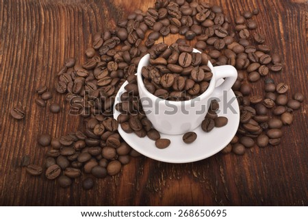 Roasted brown coffee beans & mug on wooden table