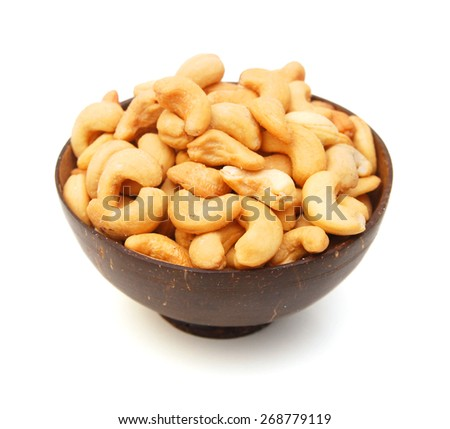 Roasted cashew nuts in wooden bowl on white background  - stock photo