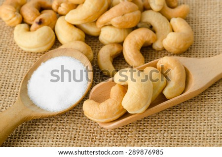 Roasted cashews and salt in wooden spoon on natural sack background - stock photo