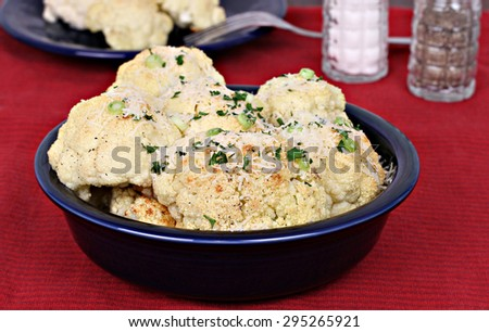 Roasted cauliflower with a sprinkle of parmesan cheese.  Selective focus on front. - stock photo