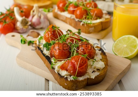 Roasted Cherry Tomato Sauce and Ricotta on Toast, fresh squeezed orange juice with lime, bio garlic and microgreens on tomato, baked with thyme - stock photo