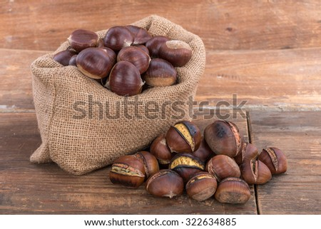 Roasted chestnuts and burlap bag full of raw chestnuts  - stock photo