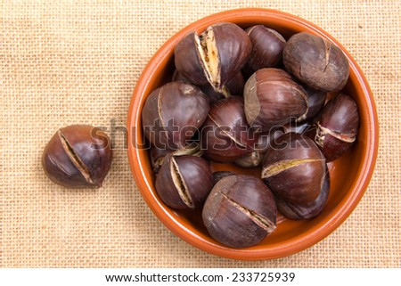 Roasted chestnuts in bowl on placemat jute top view - stock photo