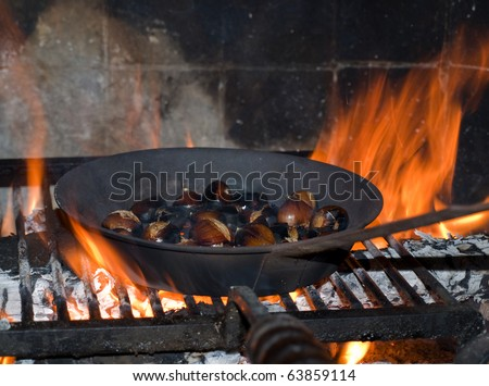 roasted chestnuts in the fireplace - stock photo