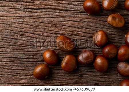 roasted chestnuts on wood background - stock photo