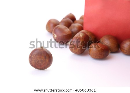 Roasted chestnuts outside red bag on white floor.
