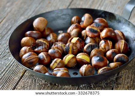 Roasted chestnuts served in a special perforated chestnut pan on an old wooden table  - stock photo