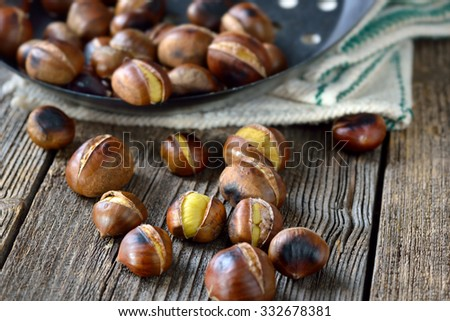 Roasted chestnuts with a perforated chestnut pan on an old wooden table with vintage linen - stock photo