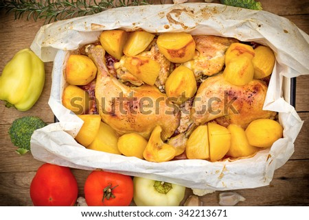 Roasted chicken and baked potatoes - stock photo