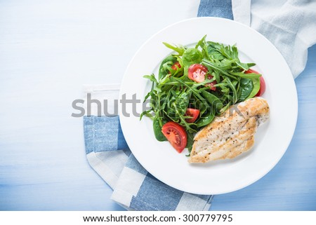 Roasted chicken breast and fresh salad with tomato and greens (spinach, arugula) top view on blue wooden background. Healthy food. - stock photo