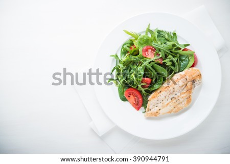 Roasted chicken breast and fresh salad with tomato and greens (spinach, arugula) top view on white wooden background. Healthy food. Space for text. - stock photo