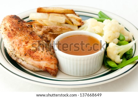 roasted chicken breast with gravy dipping sauce on the side with french fries and fresh vegetables - stock photo