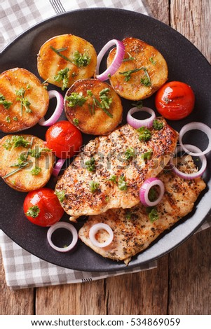 roasted chicken breast with grilled potatoes and tomatoes closeup on a ...