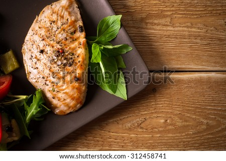 Roasted chicken breast with spices and fresh vegetables on wooden background - stock photo