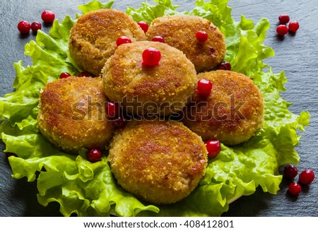 Roasted chicken cutlets on green lettuce. Dark stone background. - stock photo