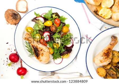 Roasted Chicken Drumstick Served with Fresh Greens and Tomato Salad - stock photo