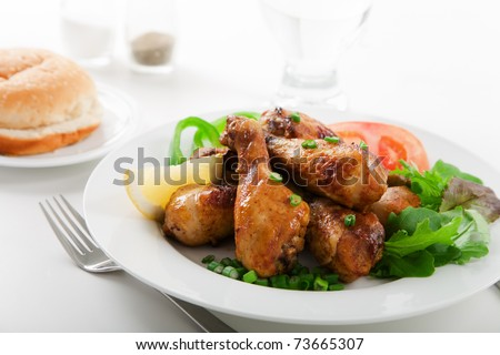 Roasted chicken drumsticks and salad on white plate - stock photo