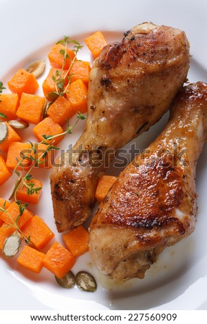 Roasted chicken drumsticks with a pumpkin on a white plate. closeup, vertical view from above