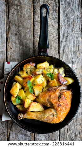 Roasted chicken leg and baked potato in the pan from above,selective focus  - stock photo