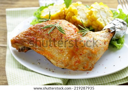 roasted chicken leg with corn for garnish - stock photo