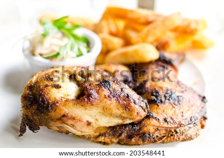 Roasted chicken leg with fries potato and herbs - stock photo