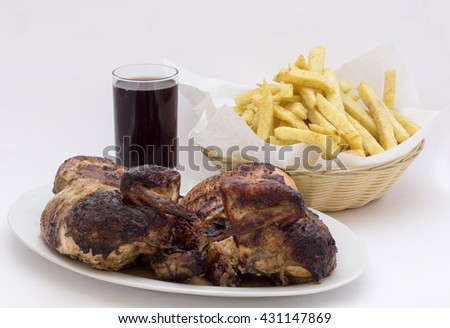 """Roasted chicken leg with fries potato called """"Pollo a la Brasa"""" in South America. Served with a glass of chicha morada, purple corn  juice.  - stock photo"""
