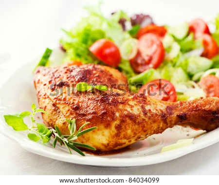Roasted chicken leg with herbs and salad - stock photo