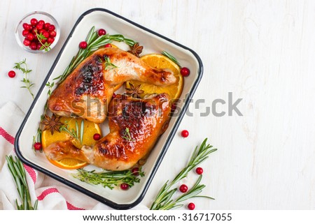 roasted chicken leg with orange and spicy herbs , top view, copy space - stock photo