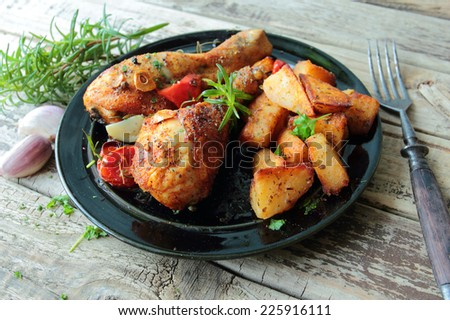 Roasted chicken legs with fried potatoes and herbs - stock photo