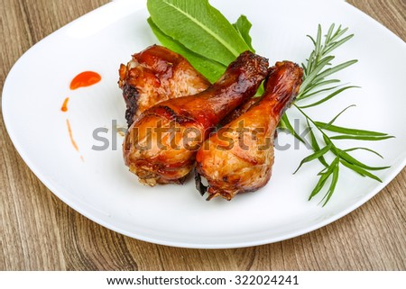 Roasted chicken legs with rosemary on the wood background