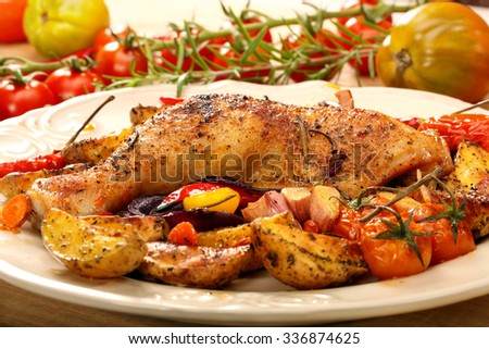 Roasted chicken legs with vegetables and herbs on wooden background
