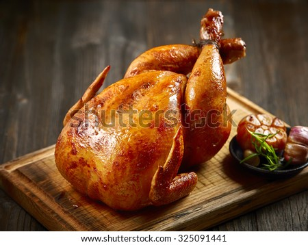 roasted chicken on wooden cutting board - stock photo