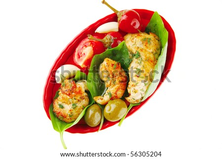 roasted chicken pieces served with vegetables on red