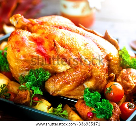 Roasted Chicken. Roasted turkey garnished with Potato, Vegetables and cranberries on a rustic style table decorated with autumn leaves and candles. Thanksgiving Dinner - stock photo
