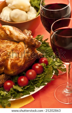 Roasted chicken (turkey) garnished with tomatoes, potatoes and wine on holiday table ready to eat - stock photo