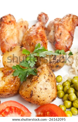 roasted chicken wings and legs with roasted potatoes, fresh tomatoes and rice with peas