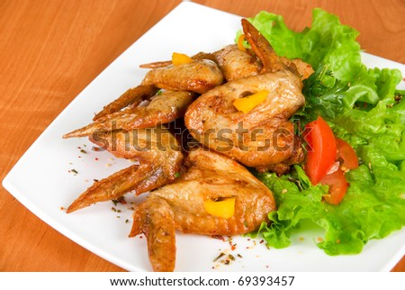 roasted chicken wings garnished with fresh green salad, pepper and greens - stock photo