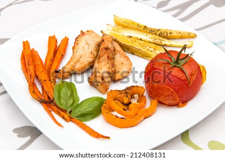 Roasted chicken with backed vegetables, healthy food, small dish - stock photo