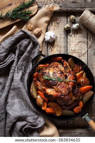 Roasted chicken with brown crispy skin stuffed with various vegetables and spices, garlic in cast iron skillet on vintage wooden table background. Rustic style, top view. - stock photo