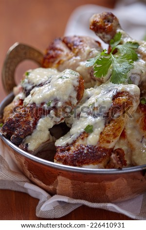 Roasted chicken with creamy garlic sauce in copper dish
