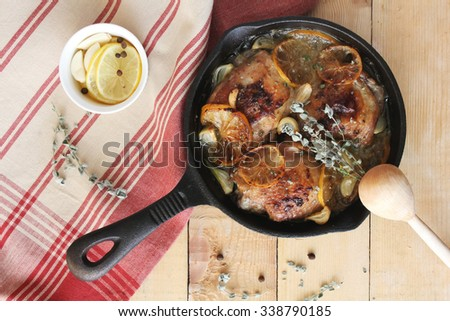 Roasted chicken with lemon and thyme in a pan on a wooden rustic table, selective focus - stock photo