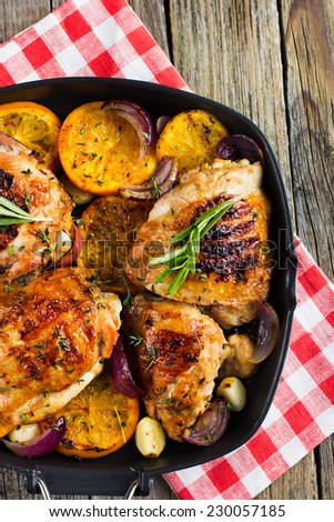 Roasted chicken with oranges and herbs, top view - stock photo