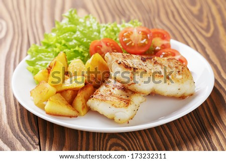 roasted codfish fillet with vegetables, selective focus - stock photo