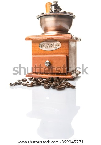 Roasted coffee bean in a wooden coffee mill over white background