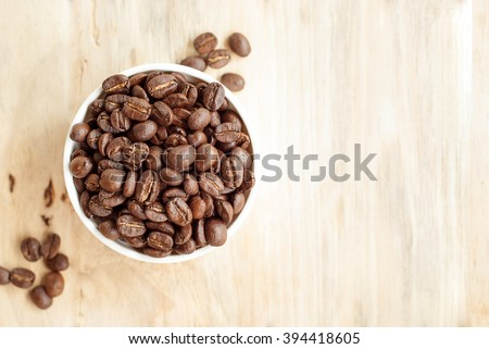 roasted coffee bean in bowl on wooden background. - stock photo
