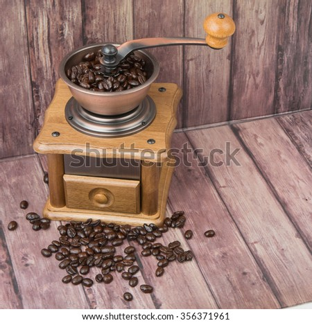 Roasted coffee bean with coffee mill over wooden background