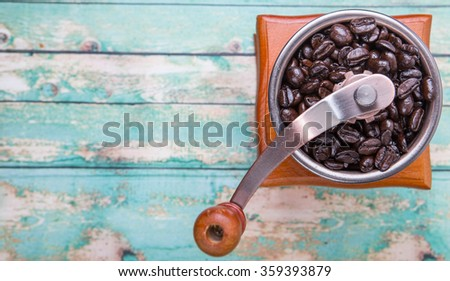 Roasted coffee bean with coffee mill over wooden background - stock photo