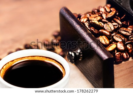 Roasted Coffee Beans and cup of black Coffee closeup. Espresso Coffee Cup on wooden background macro.