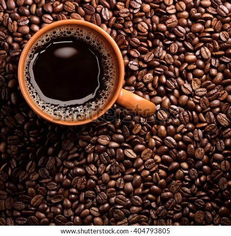 Roasted coffee beans and cup of coffee - stock photo
